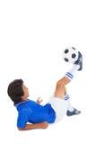 踢球的蓝色的足球运动员 库存照片