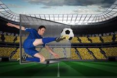 踢球的适合的足球运动员通过电视 免版税库存图片