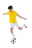 踢球的黄色球衣的足球运动员 图库摄影