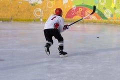 踢用棍子的行动的冰球球员 免版税库存照片