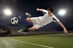 踢的足球运动员跳跃和 图库摄影