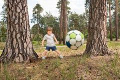 踢足球室外在公园 儿童有父亲的乐趣一起使用 库存照片