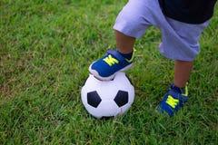 踢足球或橄榄球的亚洲孩子在公园 免版税库存图片
