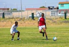 踢足球橄榄球的不同的孩子在学校 库存照片