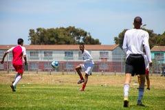踢足球橄榄球的不同的孩子在学校 图库摄影