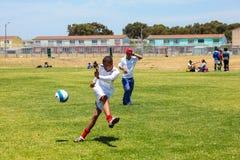 踢足球橄榄球的不同的孩子在学校 免版税库存照片