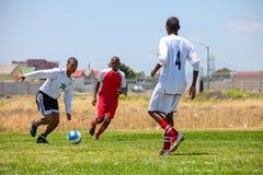 踢足球橄榄球的不同的孩子在学校 免版税库存图片