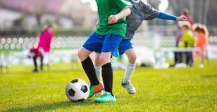踢足球比赛的孩子 踢橄榄球的年轻男孩 免版税图库摄影