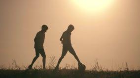 踢足球的两个男孩在日落 使用与球的孩子剪影在日落 一个愉快的家庭的概念 影视素材