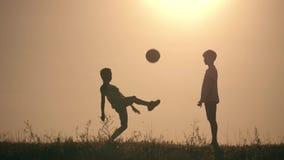 踢足球的两个男孩在日落 使用与球的孩子剪影在日落 一个愉快的家庭的概念 股票录像