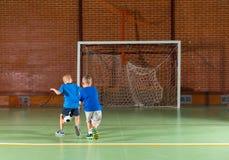 踢足球的两个年轻男朋友 免版税库存图片