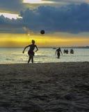 踢足球的人们在海滩 库存照片