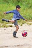 踢足球的似亚马逊盖丘亚族人的男孩 免版税库存图片
