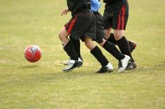 踢足球的儿童橄榄球 免版税库存照片
