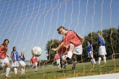 踢足球的女孩 免版税图库摄影