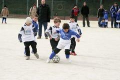 踢足球的孩子在冬天 免版税图库摄影