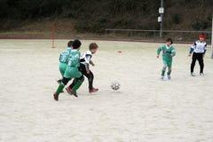 踢足球的孩子在冬天 库存图片