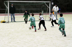 踢足球的孩子在冬天 免版税库存照片