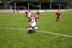 踢足球的孩子在夏天在一个室外草竞技场 免版税库存图片
