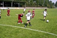 踢足球的孩子在夏天 库存图片