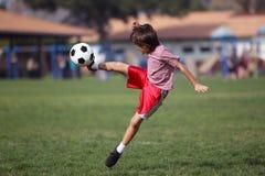 踢足球的男孩在公园 免版税库存照片
