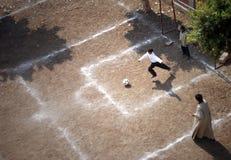 踢足球的男孩在吉萨棉 库存图片