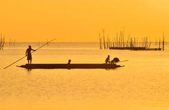 踢他的小船的渔夫在钓鱼在日落以后在宋卡湖,宋卡,泰国的Souhtern 图库摄影
