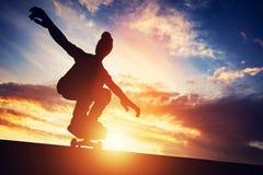 踩滑板在日落的人 免版税库存照片