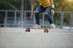 踩滑板在skatepark的溜冰板者 免版税库存照片