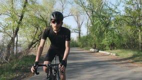 踩的踏板在马鞍外面的被聚焦的确信的骑自行车者 r 穿在自行车的专业骑自行车者黑服装 Slo 股票录像