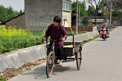 彭州,中国: 妇女骑马自行车推车 免版税库存照片