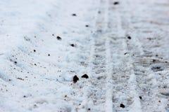 踩的踪影在雪机器的 免版税库存图片