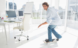 踩滑板在一个明亮的办公室的愉快的年轻人 免版税库存图片