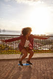 踩滑板在一座被铺的桥梁的女孩 免版税库存照片