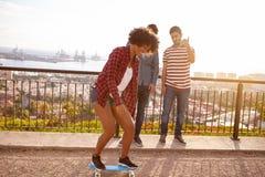 踩滑板在城市的一座桥梁 库存照片
