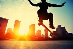 踩滑板在城市的溜冰板者 免版税库存图片