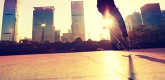 踩滑板在日出城市 免版税库存照片