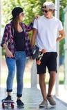 踩滑板在街道的年轻夫妇 免版税图库摄影