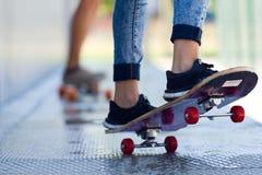 踩滑板在街道的年轻夫妇 库存照片
