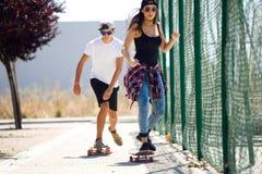 踩滑板在街道的年轻夫妇 免版税库存照片
