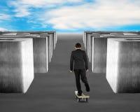 踩滑板在金钱滑板通过迷宫 免版税库存照片