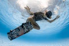 踩滑板在水面下 库存照片