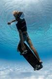 踩滑板在水面下 图库摄影