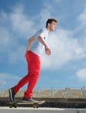 踩滑板户外在夏天的英俊的年轻人 免版税库存照片