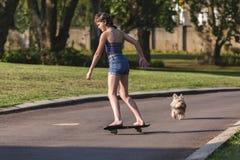 踩滑板的女孩在家 免版税图库摄影