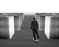 踩滑板的金钱滑板通过迷宫 免版税图库摄影
