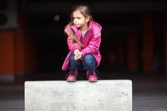蹲下一个哀伤的小女孩 免版税库存图片