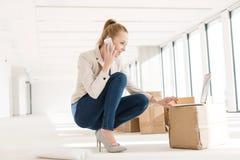 蹲下全长年轻的女实业家,当使用手机和膝上型计算机在新的办公室时 库存图片