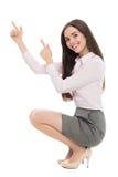 蹲下和指向手指的妇女 免版税库存图片