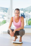 蹲下在健身房的秤的妇女 免版税图库摄影